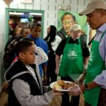 Photo taken in 2010 of a group of people in a soup kitchen, with former president Barack Obama serving lunch to a girl in line. She is wearing a black and gray hooded sweatshirt.