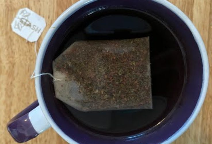 A cup of tea steeping in a white and purple mug.
