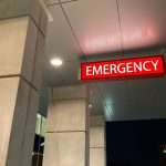 """Photo of the entrance to a hospital emergency room, or Accident and Emergency department for those in the U.K. A lighted sign that says """"Emergency"""" hangs from a gray tiled ceiling above the entrance."""