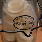 A butter jar with a black handle sits on a counter top, branded Milkhouse Candle Company, contains a batch of homemade wax melts.