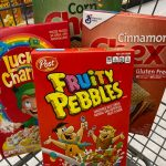 Boxes of cereal sit in a shopping cart. Clockwise from left: Lucky Charms, Corn Chex, Cinnamon Chex, and Fruity Pebbles.