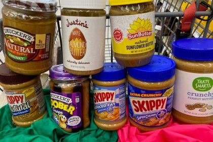 Jars of peanut and other nut butters sit in the seat of a shopping cart, stacked on top of each other.