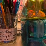An old jelly jar repurposed to serve as a place to store unused ballpoint pens in red, blue, and black, with an orange pen in the foreground, and a green one off to the left. Two rectangular pencil cases sit nearby, the bottom one in clear blue and full of pens, markers, and a mechanical pencil. Under it is a clear neon green case lined in white, which has highlighters, more pens, and an eraser inside it.