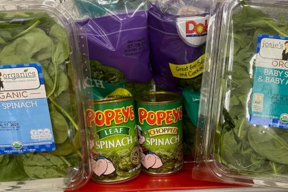 Two bags of Dole branded fresh spinach are in the back of a shopping cart seat, with one plastic container of Josie's Organics branded spinach on the far left and right sides. A can of Popeye branded leaf spinach and a can of chopped spinach are in front of the Dole bags, next to each other.