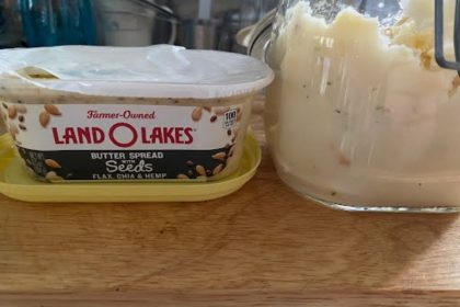 A container of Land-O-Lakes brand butter with chia seeds sits opened next to a clamp jar of instant mashed potatoes on a wood cutting board.
